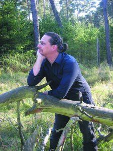 Photo von Rainer Wüst. Ein dunkelhaariger Mann um die 40 steht mit einer auf einem Zaun aufgestützten Hand im Wald und schaut nachdenklich in die Ferne.