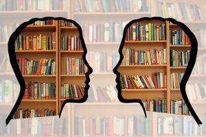 Ideenschmiede zwei Kopfe mit Bücherregal im Hintergrund